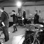 Schwarz-Weiß Bild der Band beim Auftritt